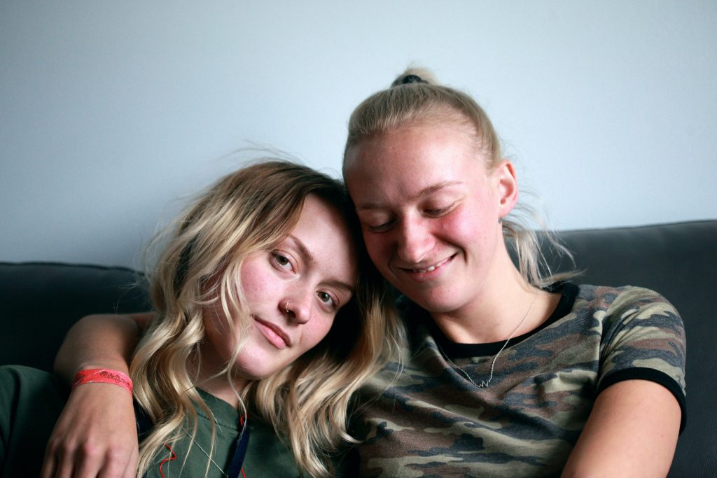 A lesbian couple hug and smile at the camera.